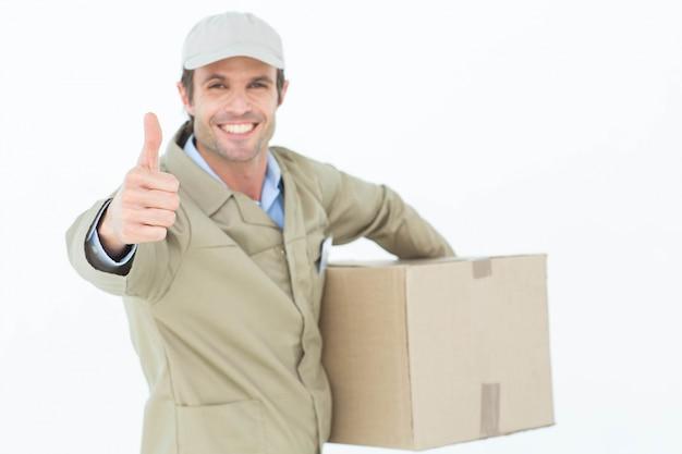 Szczęśliwy doręczeniowy mężczyzna gestykuluje aprobaty podczas gdy niosący pudełko