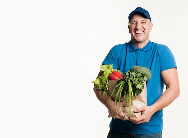 Szczęśliwy doręczeniowy mężczyzna pozuje z sklep spożywczy torbą