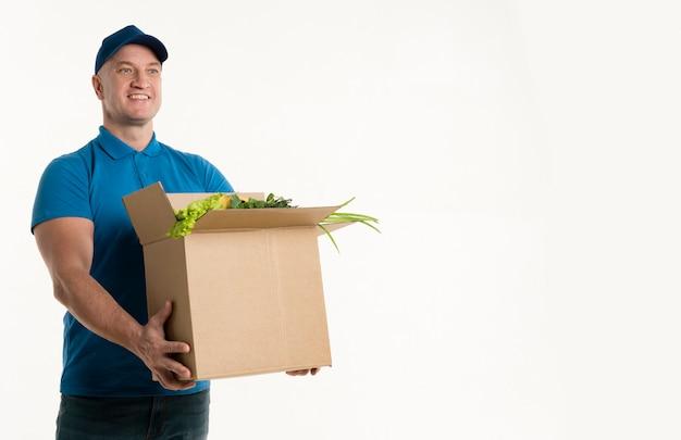 Szczęśliwy doręczeniowy mężczyzna trzyma sklep spożywczy pudełko