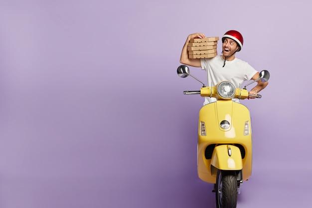 Szczęśliwy doręczyciel prowadzący skuter, trzymając pudełka po pizzy
