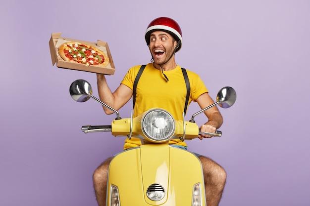 Szczęśliwy doręczyciel prowadzący żółtą hulajnogę, trzymając pudełko po pizzy
