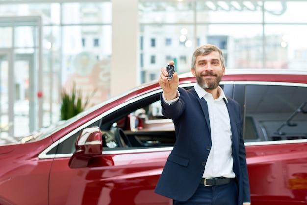 Szczęśliwy dorośleć mężczyzna przedstawia kluczyki do samochodu