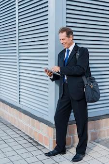Szczęśliwy dorośleć mężczyzna używa cyfrową pastylkę przy outdoors