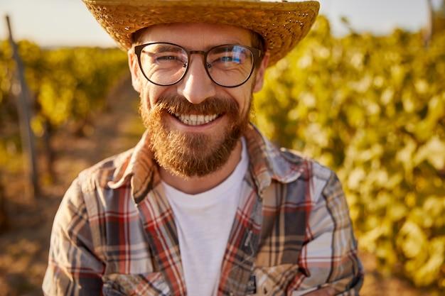 Szczęśliwy dorosły brodaty właściciel firmy rolnej w kraciastej koszuli i słomkowym kapeluszu z okularami uśmiechający się jasno i patrząc w kamerę, stojąc w winnicy latem