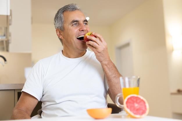 Szczęśliwy dorosły człowiek je owoce i zdrową żywność na śniadanie