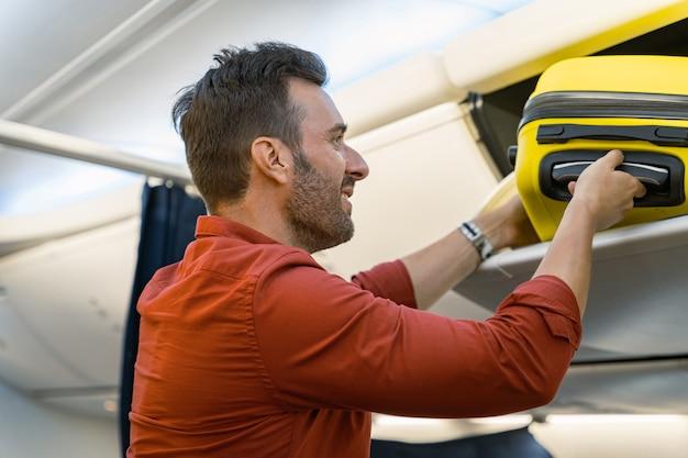 Szczęśliwy dorosły mężczyzna kładzie walizkę na półce w samolocie