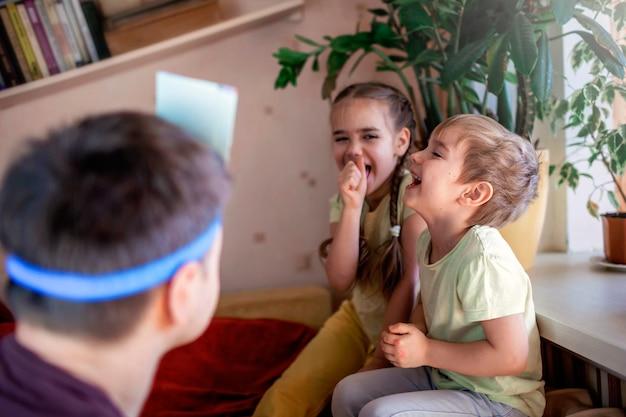 Szczęśliwy dorosły ojciec grający w grę planszową z dwójką dzieci w domowym wnętrzu, wartości rodzinne, pobyt w domu, życie podczas kwarantanny