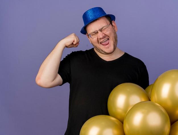 Szczęśliwy dorosły słowiański mężczyzna w okularach optycznych w niebieskim kapeluszu imprezowym podnosi pięść w górę stojąc z balonami z helem