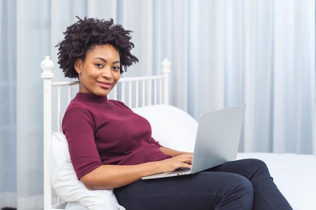 Szczęśliwy dorywczo piękna amerykańska afrykańska kobieta pracuje na komputerze przenośnym, siedząc na łóżku w domu.