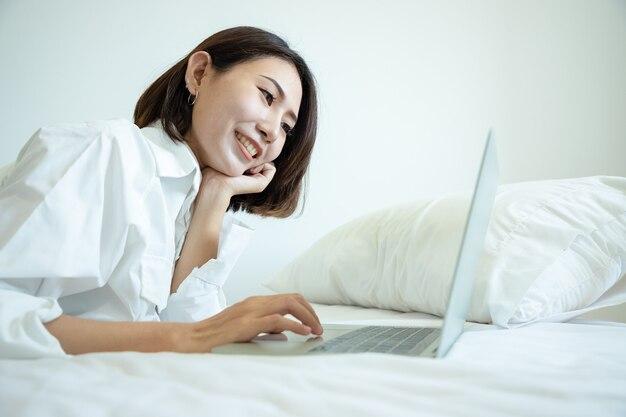 Szczęśliwy dorywczo piękna azjatycka kobieta pracuje na laptopie r. na łóżku w domu.