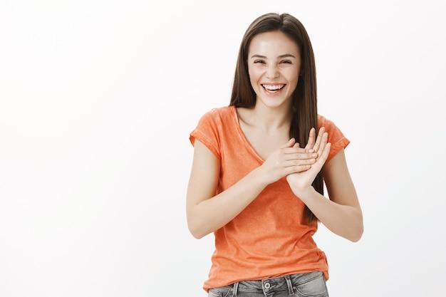 Szczęśliwy dość kaukaski dziewczyna śmiejąc się i klaszcząc w ręce, brawo