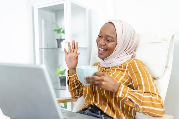 Szczęśliwy dość muzułmańskiej afryki za pomocą laptopa siedząc na wygodnej kanapie. piękna młoda muzułmanka korzysta z laptopa i uśmiecha się siedząc na kanapie w domu
