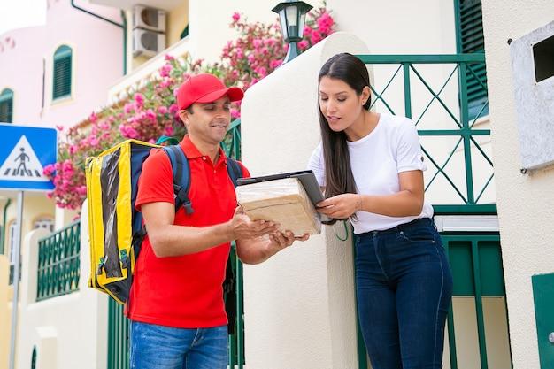 Szczęśliwy dostawca trzymający schowek podczas podpisywania klienta. całkiem długowłosa kobieta odbiera paczkę. uśmiechnięty kurier niosący plecak termiczny i dostarczający zamówienie. usługa dostawy i koncepcja poczty