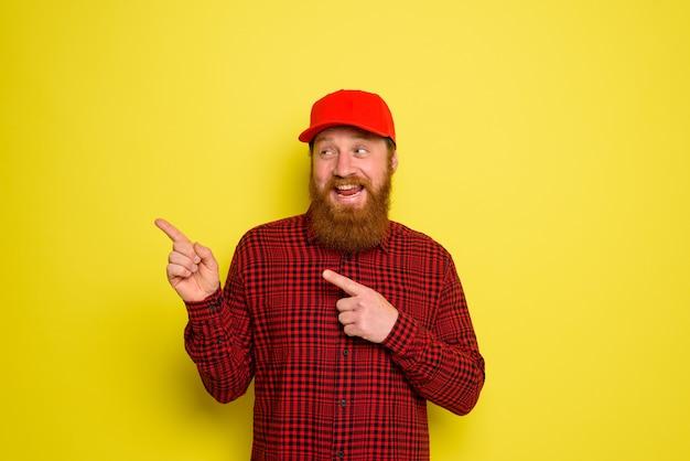 Szczęśliwy dostawca w kapeluszu i brodzie wskazuje coś be