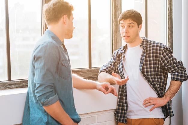 Szczęśliwy dwa męski przyjaciel stoi blisko okno gestykuluje