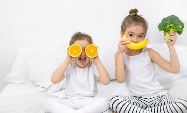 Szczęśliwy dwa słodkie dzieci bawiące się z owocami i warzywami.