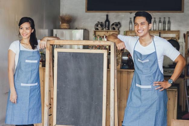 Szczęśliwy dwóch właścicieli małych firm gotowy do otwarcia kawiarni
