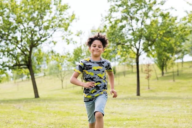 Szczęśliwy dysponowany młody chłopiec bieg w kierunku kamery