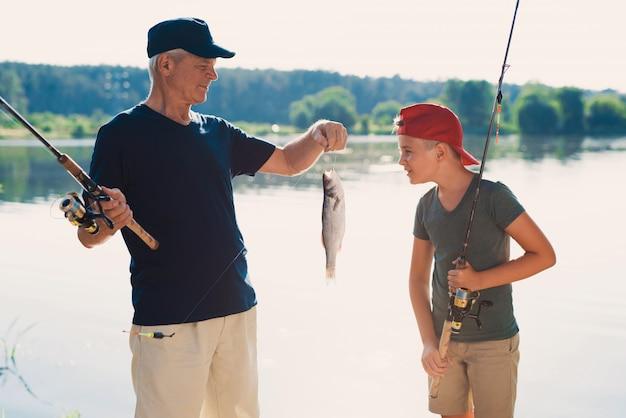 Szczęśliwy dziadek i wnuczek połowów na rzece.