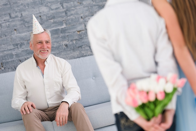 Szczęśliwy dziadek patrząc na swoje wnuki ukrywające prezenty za plecami