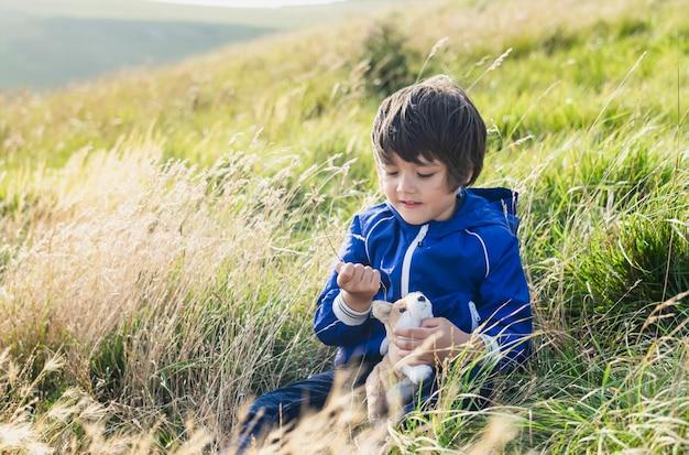 Szczęśliwy dzieciak bawiący się słomianą trawą siedzi na łące na wzgórzu, chłopiec dziecko siedzi na trawie na polu gospodarstwa grając na świeżym powietrzu ze swoją zabawką