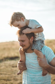 Szczęśliwy dzieciak bawiący się z ojcem. tata i syn na zewnątrz. ojciec niosący dziecko na plecach. szczęśliwa rodzina w letnim polu.