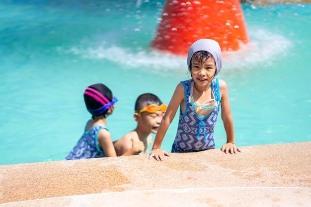 Szczęśliwy dzieciak bawić się na pływackim basenie na dniu