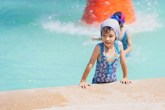 Szczęśliwy dzieciak bawić się na pływackim basenie