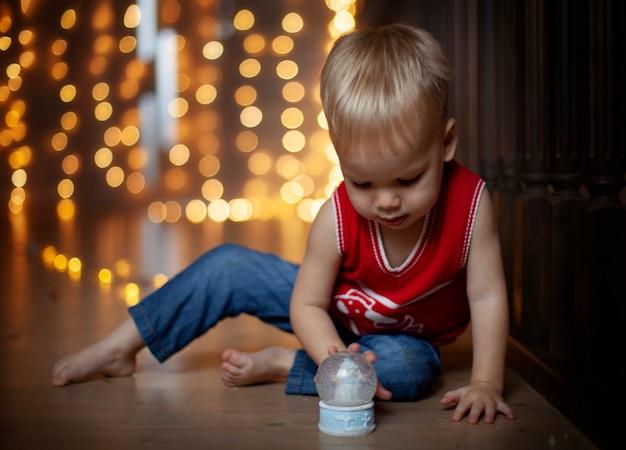Szczęśliwy dzieciak bawić się w boże narodzenie kulą