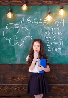 Szczęśliwy dzieciak dziewczyna czytanie książki. powrót do koncepcji szkoły i dzieciństwa.