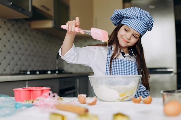 Szczęśliwy dzieciak dziewczyna wyrabia ciasto