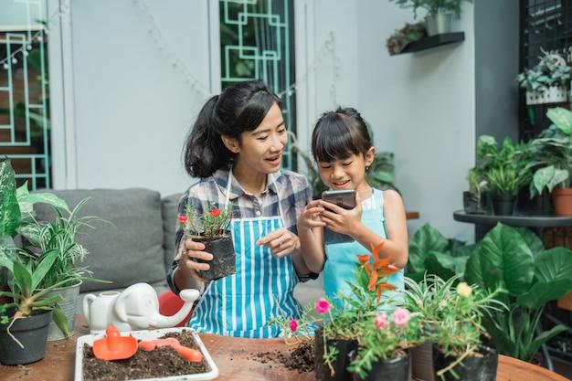 Szczęśliwy dzieciak i matka uprawia ogródek w domu