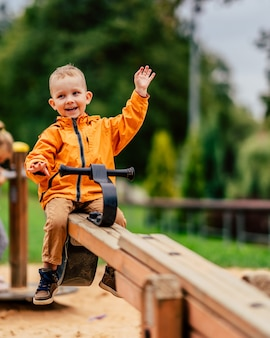 Szczęśliwy dzieciak macha z huśtawek na placu zabaw