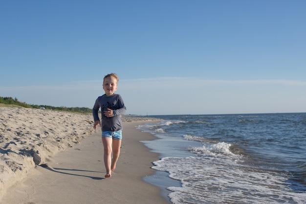 Szczęśliwy dzieciak na plaży morskiej