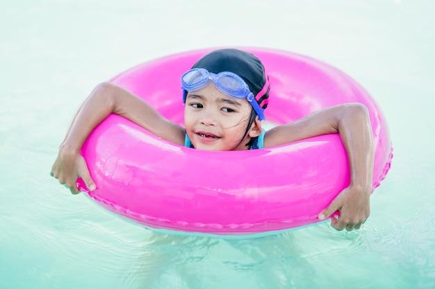 Szczęśliwy dzieciak pływa w zbawczej ringowej gumie w basenie