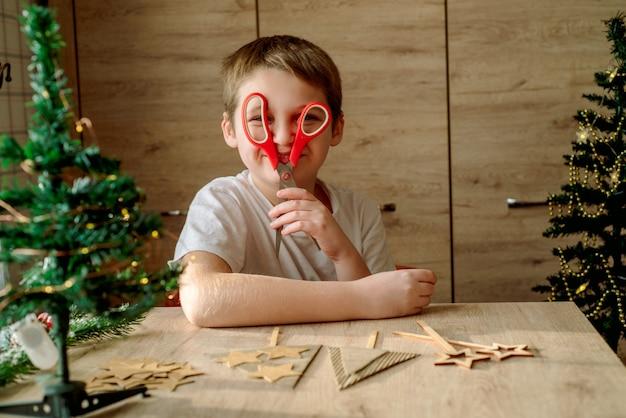 Szczęśliwy dzieciak robi choinkę z kartonu. bez odpadów, ekologiczne trendy, zero odpadów.