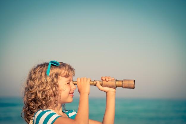 Szczęśliwy dzieciak używający lunety na tle morza i nieba w lecie