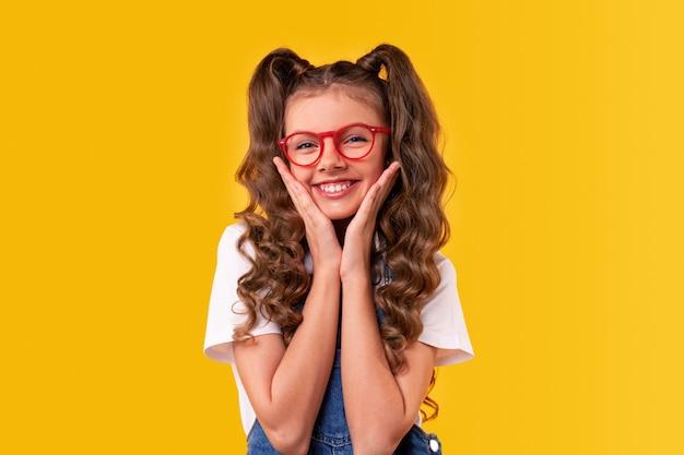 Szczęśliwy dzieciak w modnych okularach, dotykając policzków i patrząc z uśmiechem