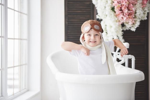 Szczęśliwy dzieciak w pilotowym kapeluszu bawić się w łazience. dzieciństwo. fantazja, wyobraźnia.