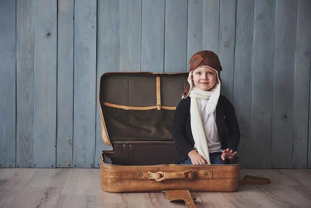 Szczęśliwy dzieciak w pilotowym kapeluszu bawić się z starą walizką. dzieciństwo. fantazja, wyobraźnia. wakacje
