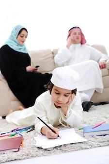 Szczęśliwy dziecko pracuje na pracie domowej w domu z jego rodziną