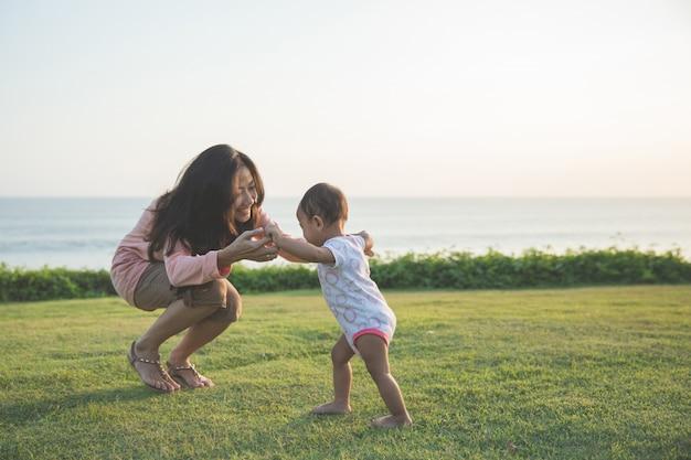 Szczęśliwy dziecko robi jego pierwszym krokom na zielonej trawie