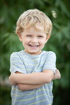 Szczęśliwy dziecko z błękitną koszulką w ogródzie