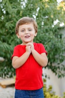 Szczęśliwy dziecko z czerwoną koszulką w ogródzie
