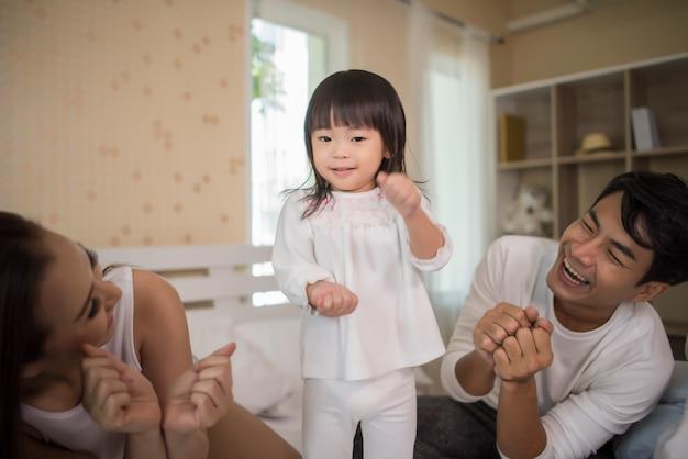 Szczęśliwy dziecko z rodzicami bawić się w łóżku w domu