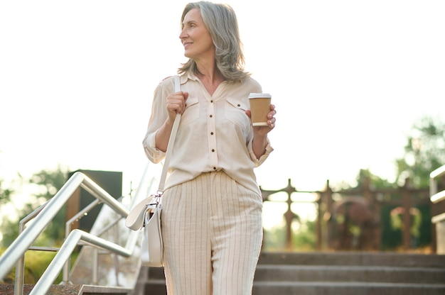 Szczęśliwy dzień. całkiem dorosła elegancka kobieta z kawą patrząc na bok na schodach w parku w letni dzień