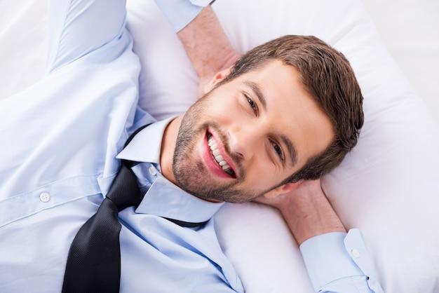 Szczęśliwy dzień marzyciel. widok z góry na przystojnego młodego mężczyznę w koszuli i krawacie, trzymający się za ręce za głową i uśmiechnięty leżąc w łóżku