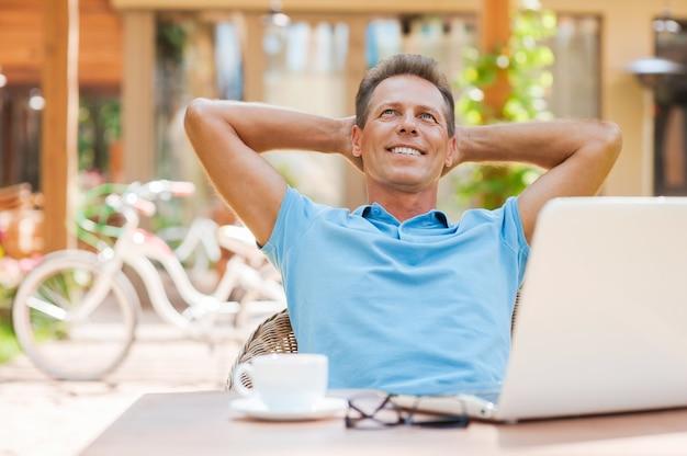 Szczęśliwy dzień marzyciel. zrelaksowany dojrzały mężczyzna trzymający się za ręce za głową i uśmiechający się siedząc przy stole na zewnątrz z laptopem na nim