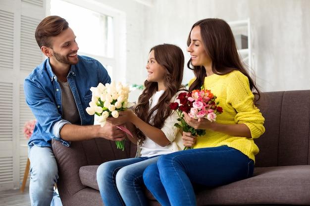 Szczęśliwy dzień matki lub dzień kobiet. podekscytowana i urocza rodzina świętująca dzień kobiet. mąż przygotował niespodziankę dla żony i małej uroczej córeczki