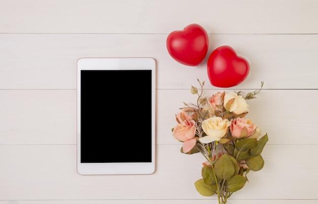 Szczęśliwy dzień matki lub walentynki symbol serca i tablet pokazując puste i kwiat na drewnianym stole